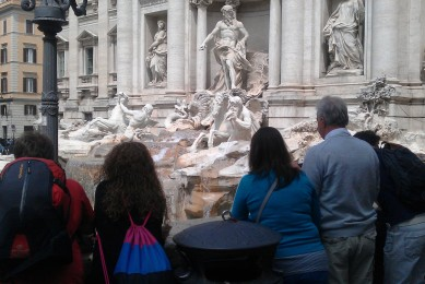 Tourists contemplating the Trevi Fountain in Rome