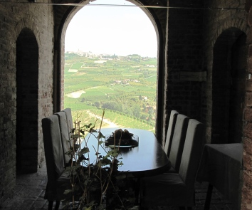 Table and chairs in front of a window overlooking grapevines